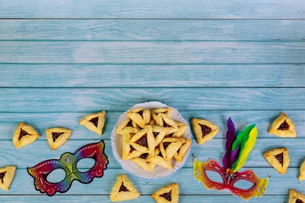 Purim-masker en driehoekskoekjes op wit Premium Foto
