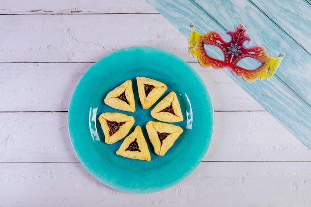 Purim met masker en driehoekige koekjes. Premium Foto