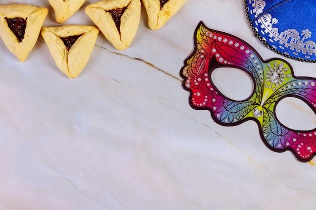 Purim met masker, kippa en koekjes. Premium Foto