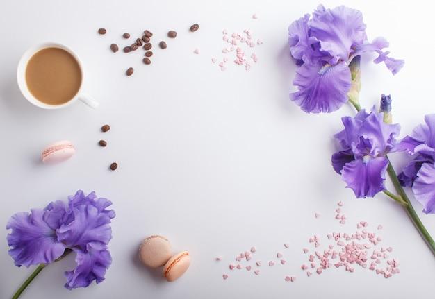 Purpere irisbloemen en een kop van koffie op wit Premium Foto