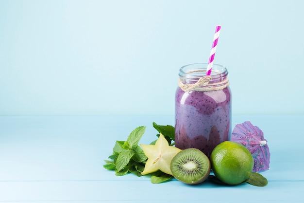 Purpere smoothiekruik op blauwe achtergrond Gratis Foto