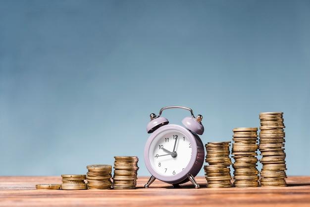 Purpere wekker tussen de stapel toenemende muntstukken op houten bureau tegen blauwe achtergrond Premium Foto