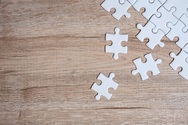 Puzzel stukjes op houten tafel. bedrijfsoplossingen, missiedoel Premium Foto
