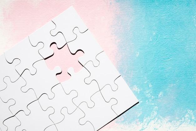 Puzzelspel met ontbrekend stuk op gestructureerde gekleurde achtergrond Gratis Foto