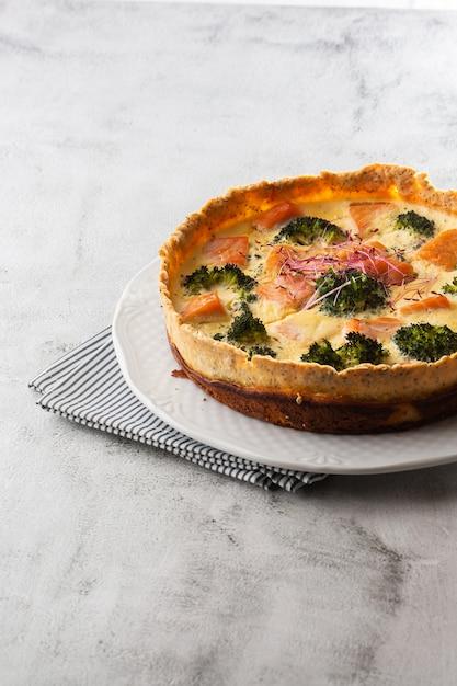 Quiche taart, bovenaanzicht. uitzicht van boven. klassieke quiche van zalm en broccoli gemaakt van korstdeeg met broccoliroosjes en gerookte zalm in een romig scharrelkoekje met vrije uitloop op tafel. Premium Foto