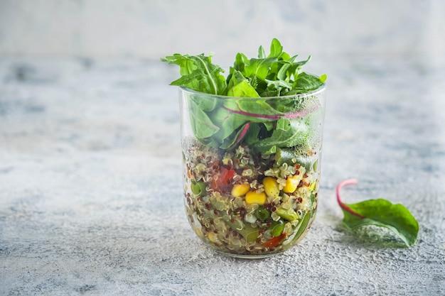 Quinoa met groenten in een glazen beker met slabladeren Premium Foto