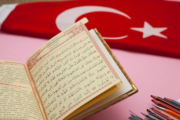 Quran en turkse vlag op de roze tafel. arabisch concept. Premium Foto