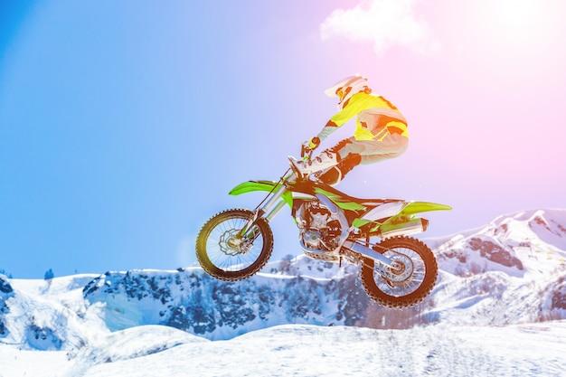 Racer op een motorfiets tijdens de vlucht, springt en vertrekt op een springplank tegen de besneeuwde bergen Premium Foto