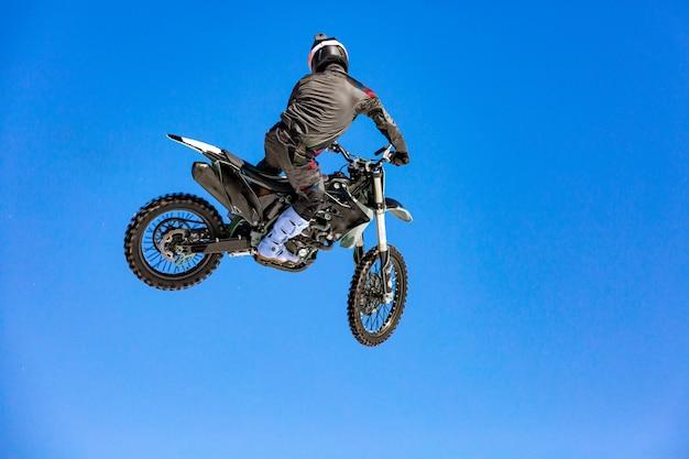 Racer op een motorfiets tijdens de vlucht, springt en vertrekt op een springplank tegen de blauwe hemel Premium Foto