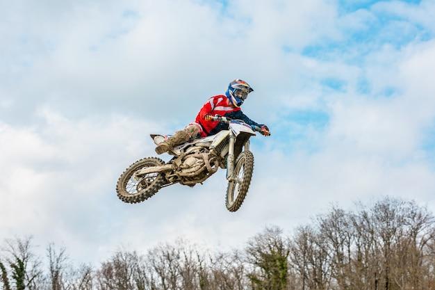 Racer op een motorfiets tijdens de vlucht, springt en vertrekt op een springplank tegen de hemel. Premium Foto