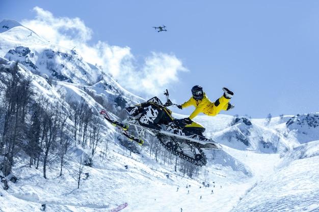 Racer op een sneeuwkat tijdens de vlucht, springt en vertrekt op een springplank tegen de besneeuwde bergen Premium Foto