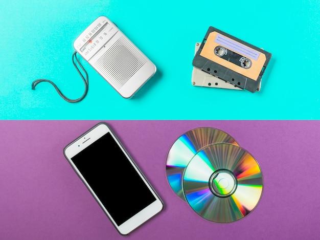 Radio; cassette; cd en mobiele telefoon op dubbel gekleurde achtergrond Gratis Foto