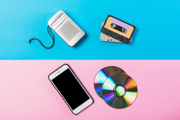 Radio; cassette; cd en mobiele telefoon op dubbele roze en blauw gekleurde achtergrond Gratis Foto