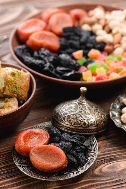 Ramadan droogde ruwe organische droge vruchten in de metaalplaat op houten geweven achtergrond Gratis Foto