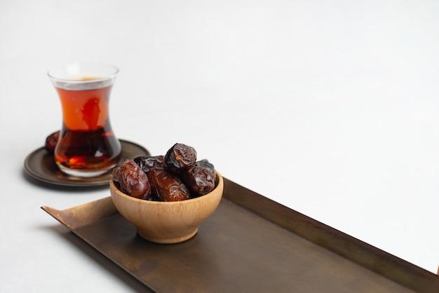 Ramadan kareem festival, data in houten kom met kopje zwarte thee Premium Foto