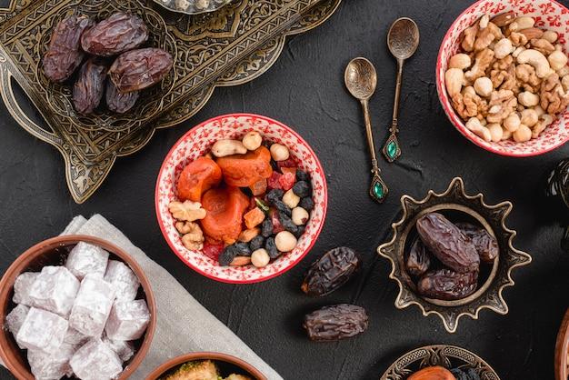 Ramadan sappige dadels en gedroogde vruchten; noten en lukum op zwarte achtergrond Gratis Foto