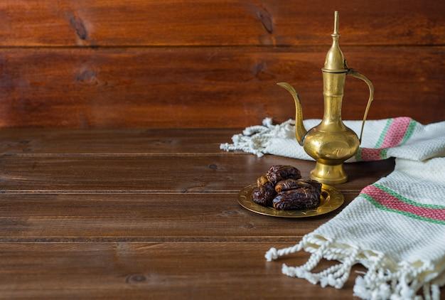 Ramadan voedselbereiding, theepot met datums, iftar voedsel op houten achtergrond met kopie ruimte Premium Foto
