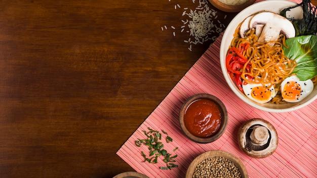 Ramennoedels in aziatische stijl met sausen op houten lijst Gratis Foto