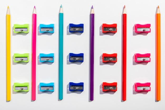 Rangschikking van kleurrijke potloden en puntenslijpers bovenaanzicht Gratis Foto