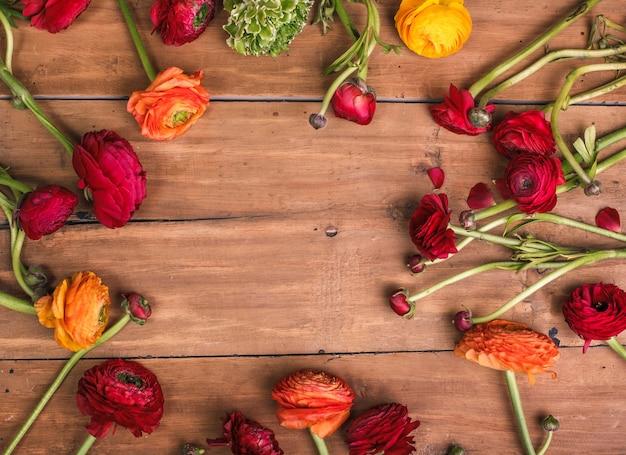 Ranunkulyus boeket van rode bloemen op een houten achtergrond Gratis Foto