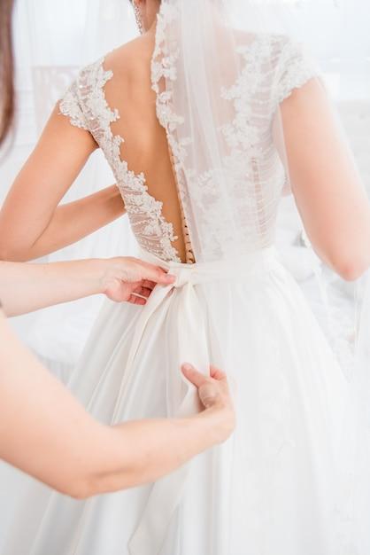 Rasp de keuze uit prachtige modejurken die hangen aan rekken in de garderobe van de vrouw. een grote variëteit aan fonkelende kleding. Premium Foto