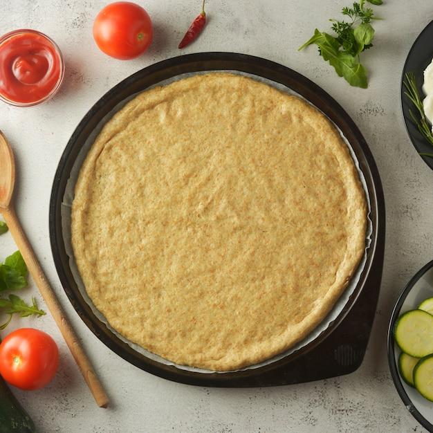 Rauw deeg en verse ingrediënten voor veganistische pizza. kopieer ruimte. Premium Foto