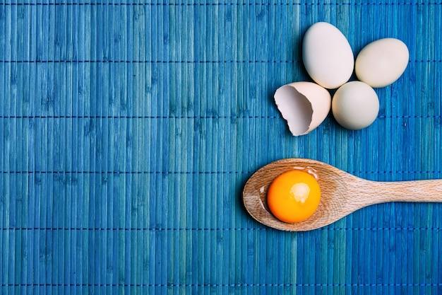 Rauw eigeel in een lepel naast eieren, op een blauwe achtergrond ecologisch. Premium Foto