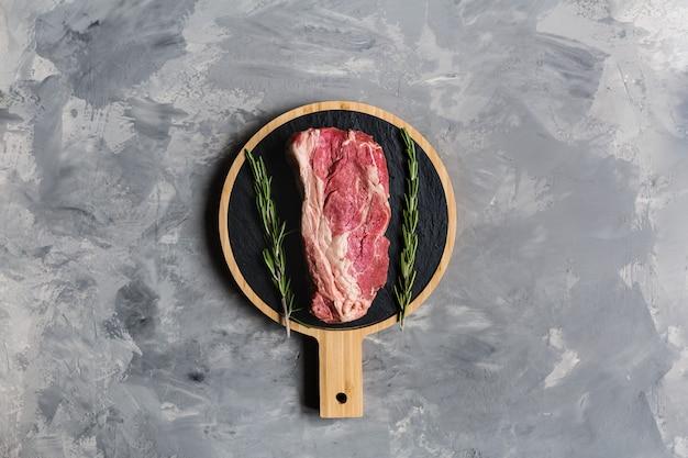 Rauw rundvlees op een snijplank met rozemarijnkruid Premium Foto