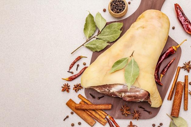 Rauw varkensvlees - spronggewricht, knokkel of been. traditioneel ingrediënt voor eisbein. vers vlees, droge kruiden en groenten Premium Foto