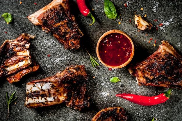 Rauw vers vlees, geroosterd of gegrild lamsvlees of rundvleesribben met rode tomatensaus, hete peper, knoflook en kruiden op donkere steen, copyspace bovenaanzicht Premium Foto