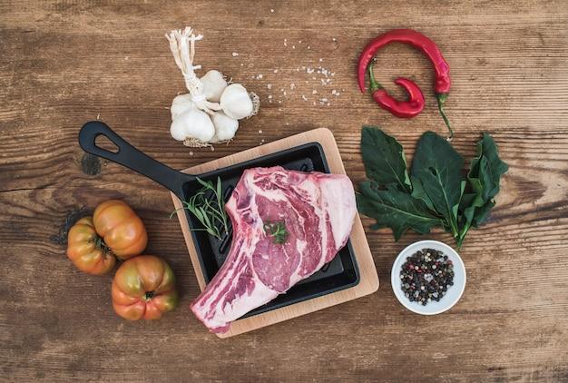 Rauw vers vlees ribeye steak met peper, zout, chili, knoflook, spinazie, heirloom tomaten en rozemarijn in kookpan Premium Foto