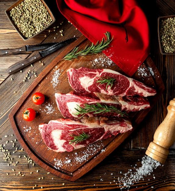 Rauw vlees plakjes gegarneerd met kruiden en zout Gratis Foto