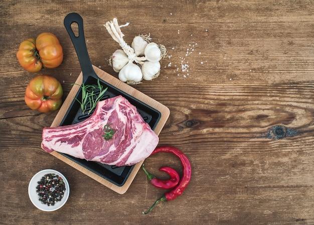 Rauw vlees ribeye steak met peper, zout, chili, knoflook, spinazie, heirloom tomaten en rozemarijn in kookpan op rustieke houten tafel Premium Foto