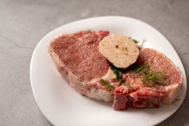 Rauw vlees. varkensvleesbiefstuk met dille in een plaat Premium Foto