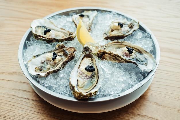 Rauwe en verse oester met kaviaar bovenop en citroen Gratis Foto