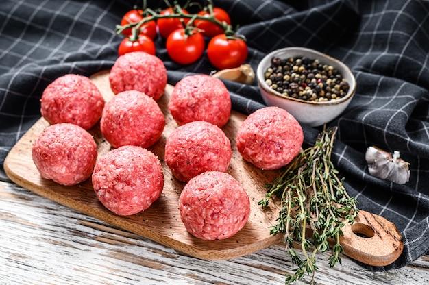 Rauwe gehaktballen, gehakt varkensvlees. witte achtergrond. bovenaanzicht Premium Foto