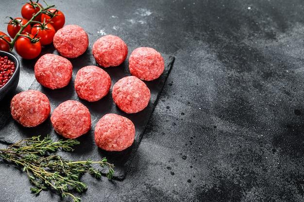Rauwe gehaktballen, gehakt varkensvlees. zwarte achtergrond. bovenaanzicht. kopieer ruimte Premium Foto