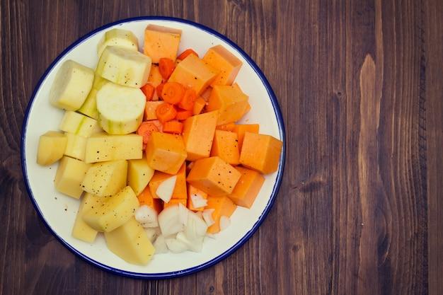 Rauwe groenten voor soep op witte plaat Premium Foto