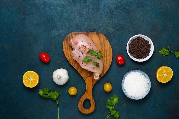 Rauwe kipfiletfilets op houten snijplank met kruiden en specerijen. bovenaanzicht Gratis Foto
