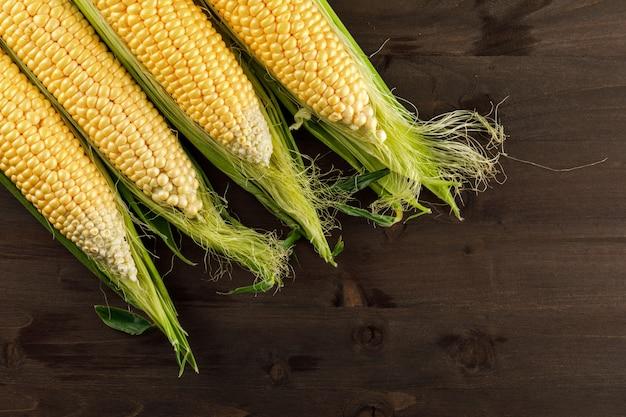 Rauwe maïs op een donkere houten tafel. plat lag. Gratis Foto