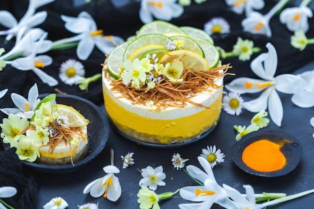 Rauwe veganistische cake met citroen en limoen op een zwarte ondergrond bedekt met kleine madeliefjebloemen Gratis Foto