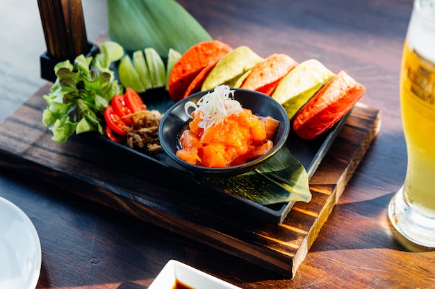 Rauwe zalm pittige salade geserveerd met rode en groene knapperige frietjes voor canapé en koud bier. Premium Foto