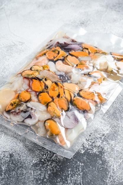 Rauwe zeevruchtenmix in vacuümverpakking. grijze achtergrond. bovenaanzicht Premium Foto