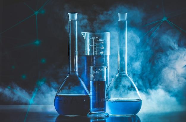 Reageerbuis en kolf met blauwe vloeistof en blauwe rook. chemie en laboratorium concept. Premium Foto