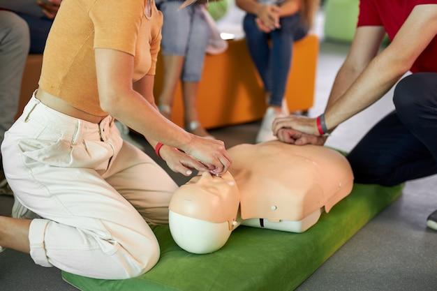Reanimatieklas met jonge blanke instructeurs die spreken en hulp eerste hulp demonstreren Premium Foto