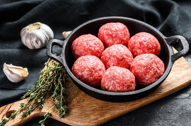 Recept voor het koken van gehaktballetjes van gehakt in een pan. zwarte achtergrond. bovenaanzicht Premium Foto