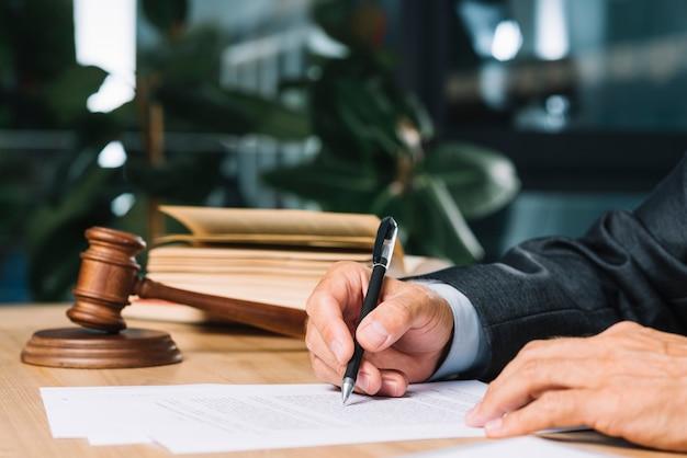 Rechter die pen houden die document over houten bureau controleren Premium Foto