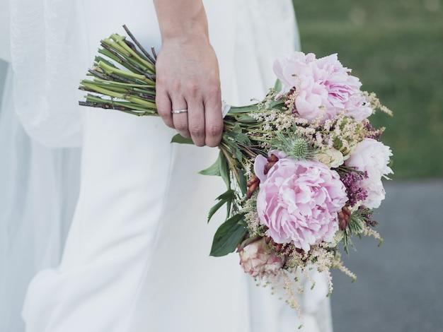 Rechterhand van een bruid die de boeketten bloemen boven haar jurk houdt Premium Foto