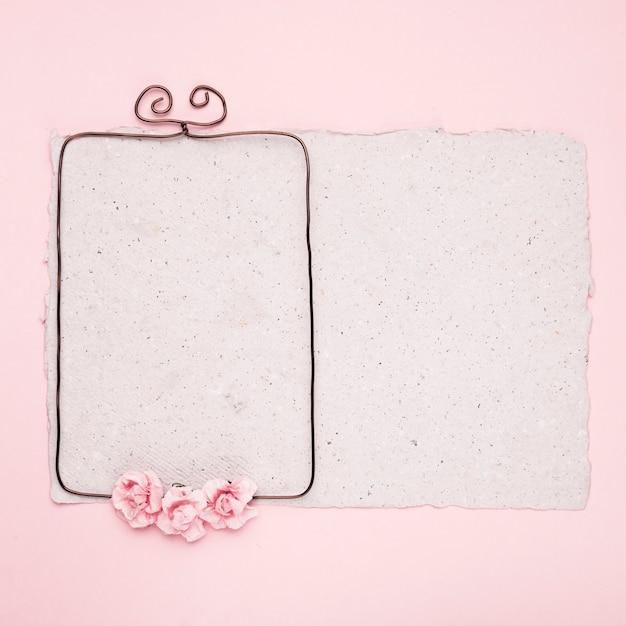 Rechthoekig draadframe versierd met rozen op papier tegen roze achtergrond Gratis Foto