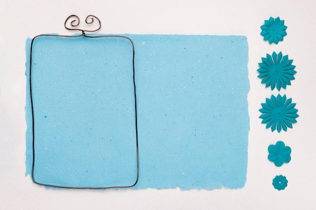 Rechthoekig kader dichtbij het blauwe document dat met bloem op witte achtergrond wordt verfraaid Gratis Foto